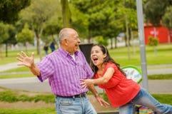 Внешний взгляд дочери и отца играя на outdoors в парке Стоковое Фото