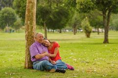 Внешний взгляд дочери обнимая ее отца с влюбленностью на outdoors сидеть в траве, в парке Стоковые Изображения RF