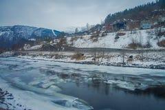 Внешний взгляд замороженного реки с некоторыми деревянными домами на одной стороне дороги на горе Gol Стоковые Изображения RF