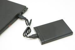 Внешний жёсткий диск соединяется к тетради компьютера Стоковые Фото