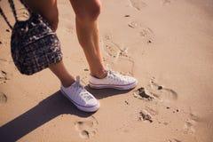 Внешний конец-вверх образа жизни ног красивого девочка-подростка Молодая женщина битника связывая шнурки в ее белых тапках Стоковые Фотографии RF