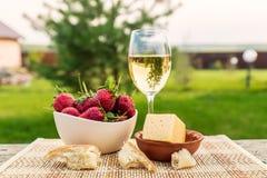 Внешний пикник весны с клубникой, сыром, хлебом и стеклом o Стоковые Фото
