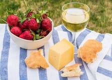 Внешний пикник весны с клубникой, сыром, хлебом и стеклом o Стоковые Фотографии RF