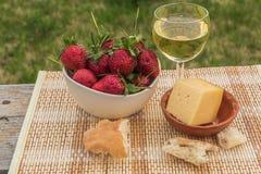 Внешний пикник весны с клубникой, сыром, хлебом и стеклом o Стоковые Изображения RF