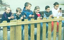 Внешний портрет девушек и мальчиков играя с телефонами Стоковые Изображения RF