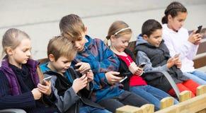 Внешний портрет девушек и мальчиков играя с телефонами Стоковое Изображение RF