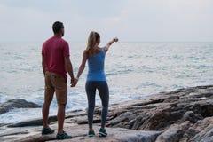 Внешний портрет лета молодых романтичных пар в влюбленности представляя на изумительном каменном пляже, Стоковые Изображения RF