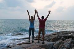 Внешний портрет лета молодых романтичных пар в влюбленности представляя на изумительном каменном пляже, Стоковая Фотография