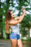 Внешний портрет красивой девушки принимая selfie с мобильным телефоном Стоковая Фотография
