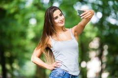 Внешний портрет красивой девушки принимая selfie с мобильным телефоном Стоковые Фото