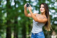 Внешний портрет красивой девушки принимая selfie с мобильным телефоном Стоковые Изображения