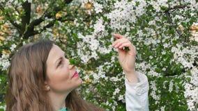 Внешний портрет красивой женщины в белой куртке среди белого дерева цветения акции видеоматериалы