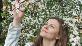 Внешний портрет красивой женщины в белой куртке среди белого дерева цветения видеоматериал