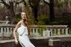 Внешний портрет лета девушки детенышей довольно милой Красивая женщина представляя на старом мосте в белых dess стоя близко камен Стоковая Фотография