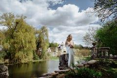 Внешний портрет лета девушки детенышей довольно милой Красивая женщина представляя на старом мосте в белых dess распологая около  Стоковое фото RF