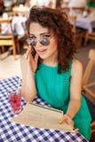 Внешний портрет милой курчавой девушки в солнечных очках имея питье в кафе Стоковые Фото