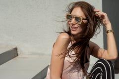 Внешний портрет молодой красивой модной счастливой дамы, нося солнечные очки, в деревянной рамке, создавая город дальше Стоковое фото RF