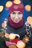 Внешний портрет молодой красивой счастливой усмехаясь девушки битника представляя на улице, смотрящ камеру, держа праздничную гир Стоковые Изображения