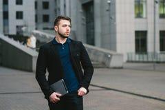 Внешний портрет молодого бизнесмена с современной таблеткой в руке на фоне делового центра Стоковое Изображение