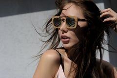 Внешний портрет молодой красивой модной счастливой дамы, нося солнечные очки, в деревянной рамке, создавая город дальше Стоковые Фото