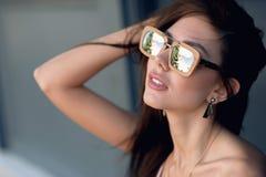Внешний портрет молодой красивой модной счастливой дамы, нося солнечные очки, в деревянной рамке, создавая город дальше Стоковое Изображение