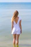 Внешний портрет молодой милой женщины в белом платье представляя в море самостоятельно Стоковые Изображения RF