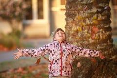 Внешний портрет молодой счастливой девушки ребенка играя с осенью l Стоковые Фотографии RF