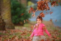 Внешний портрет молодой счастливой девушки ребенка играя с осенью l Стоковые Фото