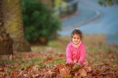 Внешний портрет молодой счастливой девушки ребенка играя с осенью l Стоковое Изображение RF