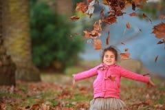 Внешний портрет молодой счастливой девушки ребенка играя с осенью l Стоковая Фотография RF