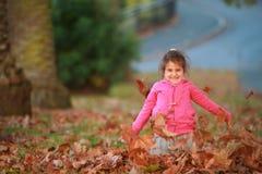 Внешний портрет молодой счастливой девушки ребенка играя с осенью l Стоковое фото RF