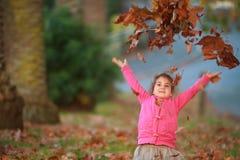 Внешний портрет молодой счастливой девушки ребенка играя с осенью l Стоковые Изображения RF