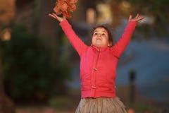 Внешний портрет молодой счастливой девушки ребенка играя с осенью l Стоковая Фотография