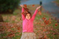 Внешний портрет молодой счастливой девушки ребенка играя с осенью l Стоковые Изображения