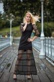 Внешний портрет образа жизни белокурой молодой женщины в стильном черном платье оставаясь на мосте на улице Осень, дождливый день Стоковые Фото