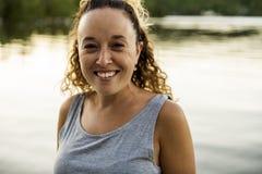 Внешний портрет прелестной женщины рядом с озером на заходе солнца стоковое изображение