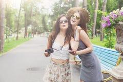 Внешний портрет 2 друзей наблюдая фото с smartphone Стоковая Фотография