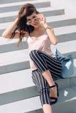 Внешний портрет солнечных очков молодой красивой модной счастливой дамы нося, в деревянной рамке, на улице города Стоковые Фотографии RF