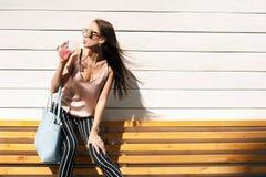 Внешний портрет солнечных очков молодой красивой модной счастливой дамы нося, в деревянной рамке, против деревянного Стоковая Фотография RF