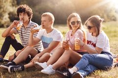 Внешний портрет счастливых девушек и их парни выпивают сидр, имеют беседу во время пикника, идя поплавать в реке, сфокусированном Стоковая Фотография