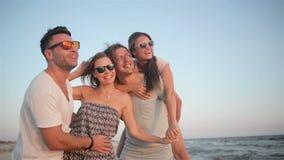Внешний портрет Active 4 люд идя на пляж на летних каникулах тратя время совместно во время ветреного акции видеоматериалы