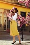 Внешний полный портрет тела молодой красивой модной счастливой дамы представляя около цветя дерева Модельный носить стильный Стоковые Фотографии RF