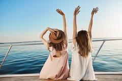 Внешняя задняя съемка молодой женщины 2 на роскошных каникулах, развевая на взморье пока сидящ на яхте Лучшие други Стоковые Фотографии RF
