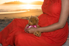 Внешняя съемка молодой беременной женщины в красном платье сидя на пляже и держа игрушку плюшевого медвежонка в ее руках Стоковые Изображения