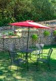 Внешняя таблица кафа на зеленой лужайке под красной сенью стоковые фотографии rf