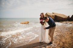 Внешняя церемония свадьбы на пляже около моря, стильный счастливый усмехаясь groom и невеста имеют потеху и смеяться над Стоковое Фото
