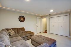 Вниз живущая комната с большой угловой софой стоковые изображения
