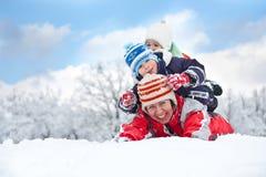 вниз семья кладя снежок Стоковая Фотография
