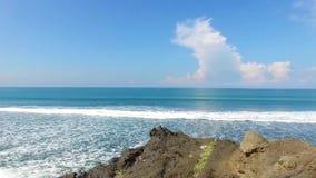 Вниз со скалы коралла на побережье пляжа Бали, Индонезия, к изменчивому морю Экологические концепции устойчивости сток-видео