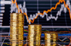 Вниз стога тенденции золотистых монеток и финансовохозяйственной диаграммы Стоковая Фотография